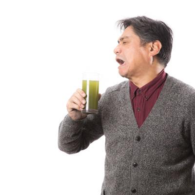 「苦くて濃い青汁を飲んで渋い顔をする中年男性」の写真素材