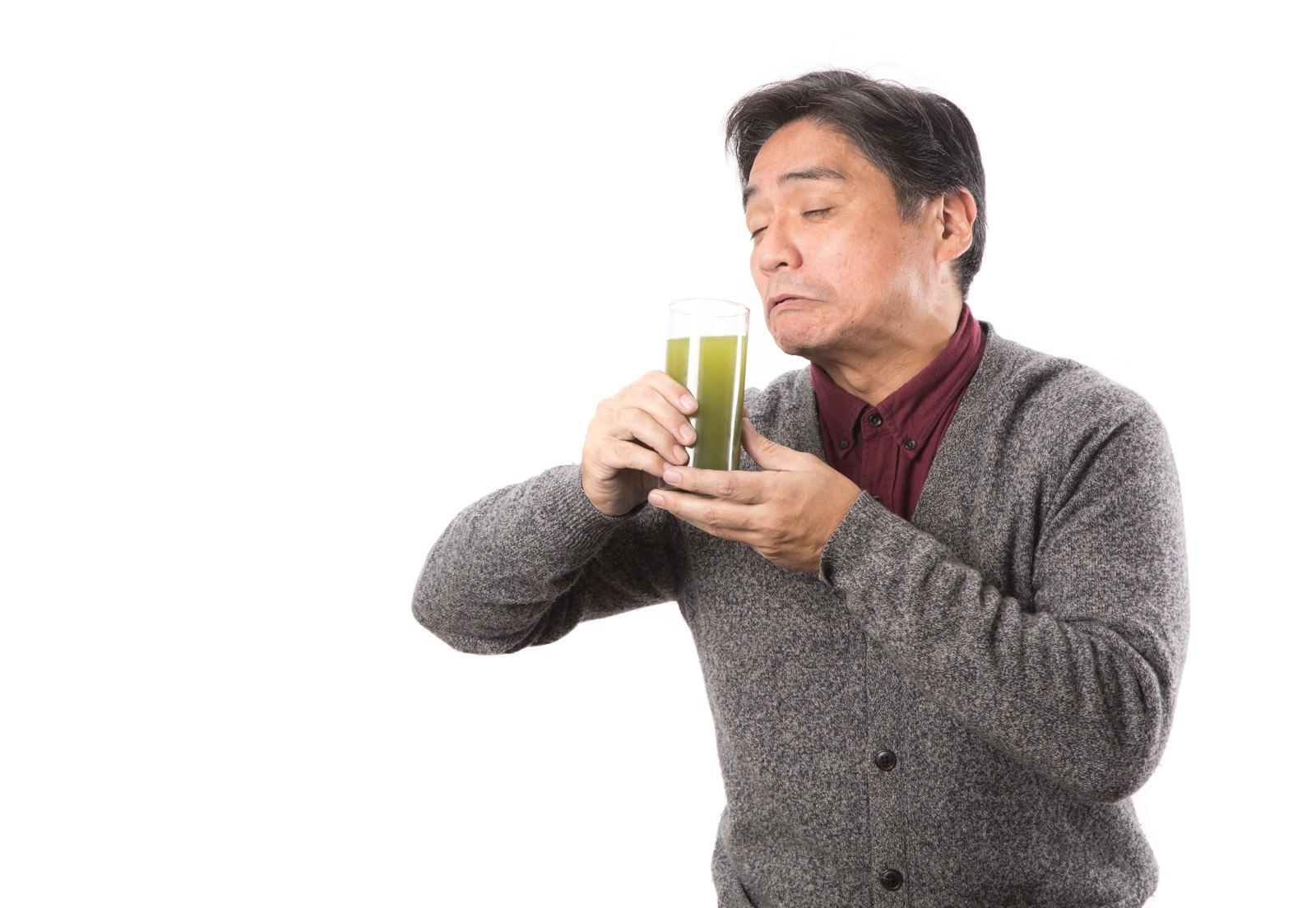 「苦手な青汁をすすり飲むお父さん」の写真[モデル:よたか]
