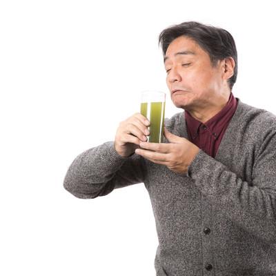 「苦手な青汁をすすり飲むお父さん」の写真素材
