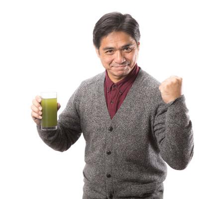 「青汁を飲んで元気だしてこ!(中年男性)」の写真素材