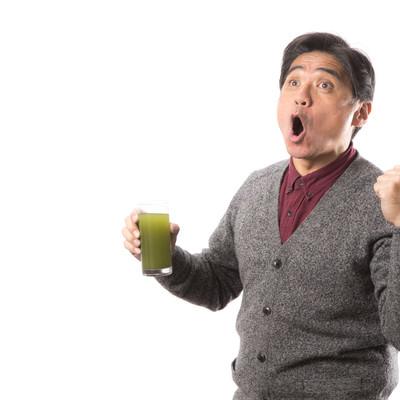 「青汁を飲みながら雄叫びをあげるお父さん」の写真素材