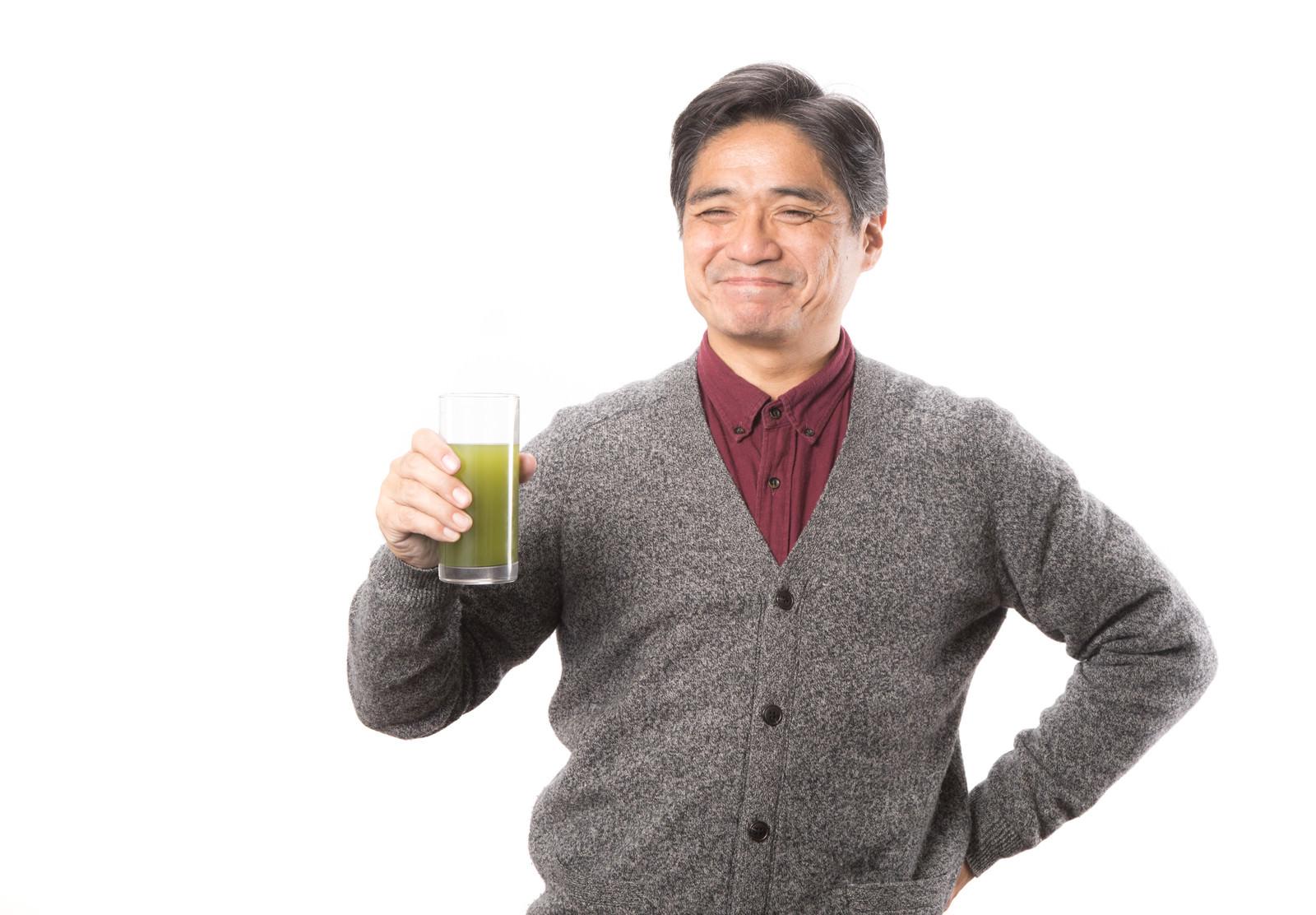 「幸せそうな顔で青汁を飲み続ける中年男性」の写真[モデル:よたか]