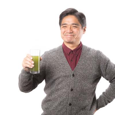 「幸せそうな顔で青汁を飲み続ける中年男性」の写真素材