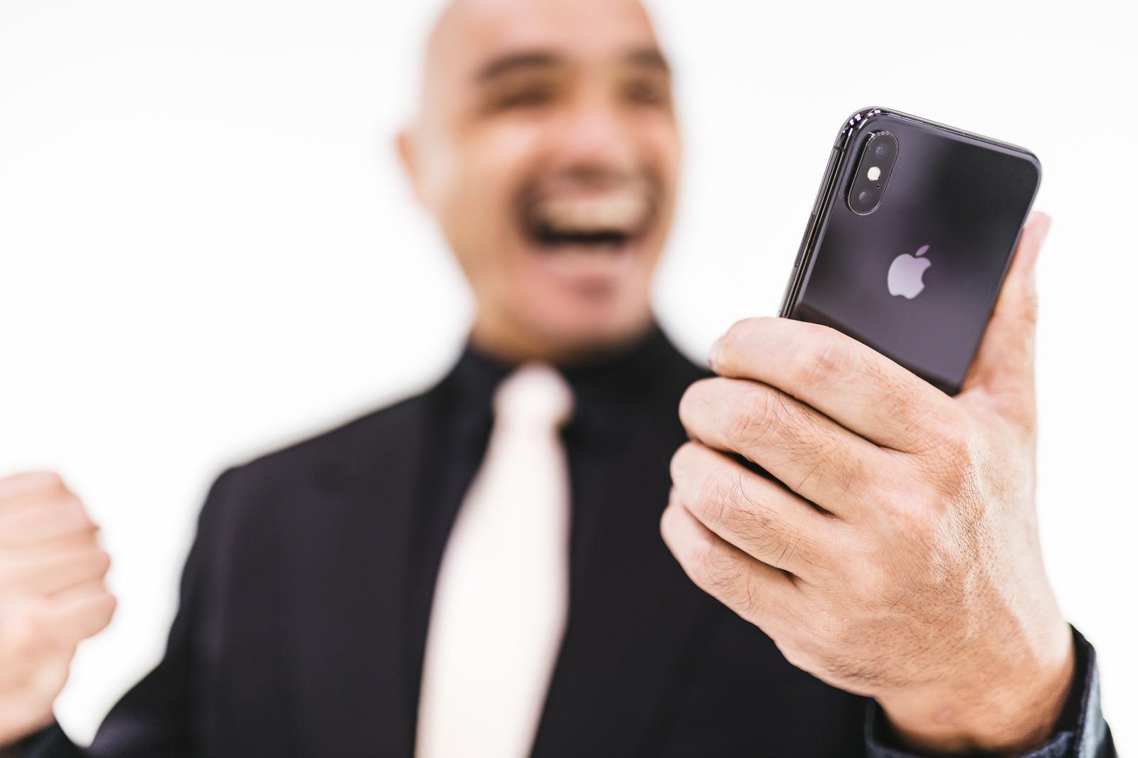「スマホを見て歓喜する強面のおっさん」の写真[モデル:よたか]