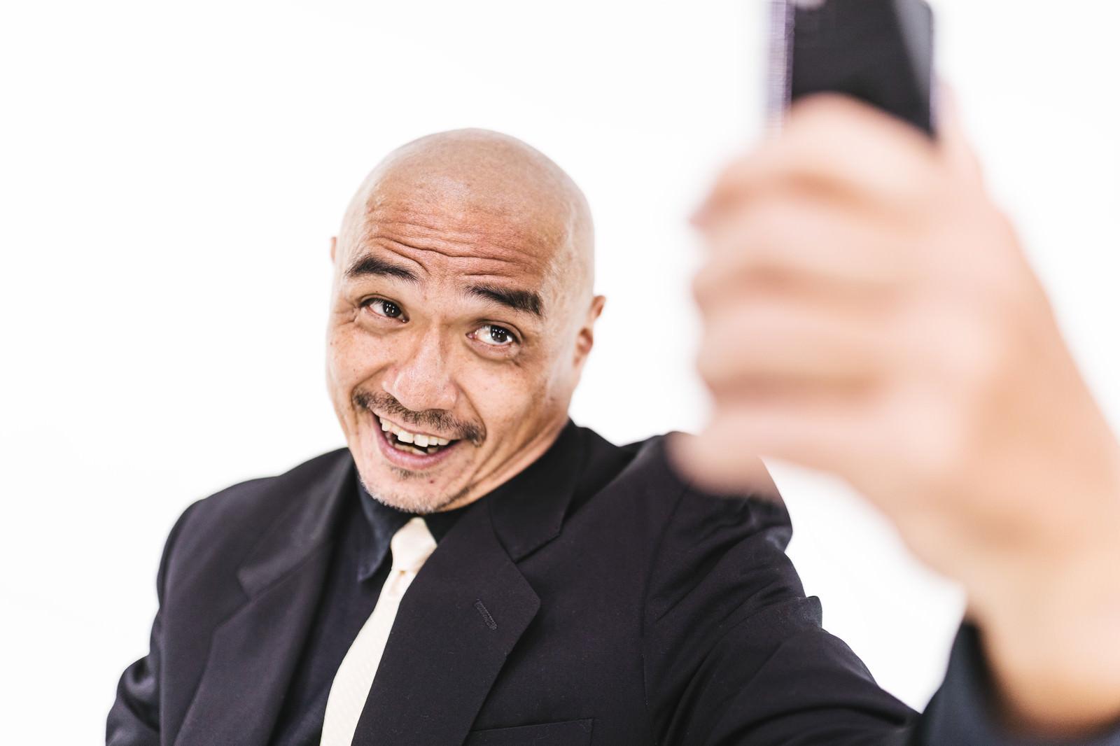 「自撮り画像を送るスキンヘッドの強面中年」の写真[モデル:よたか]