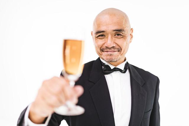 乾杯をするスキンヘッドの中年の紳士の写真