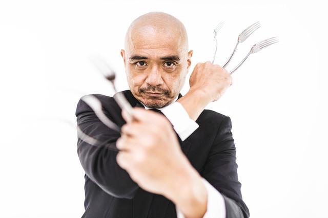 フォークで武装する強面執事の写真
