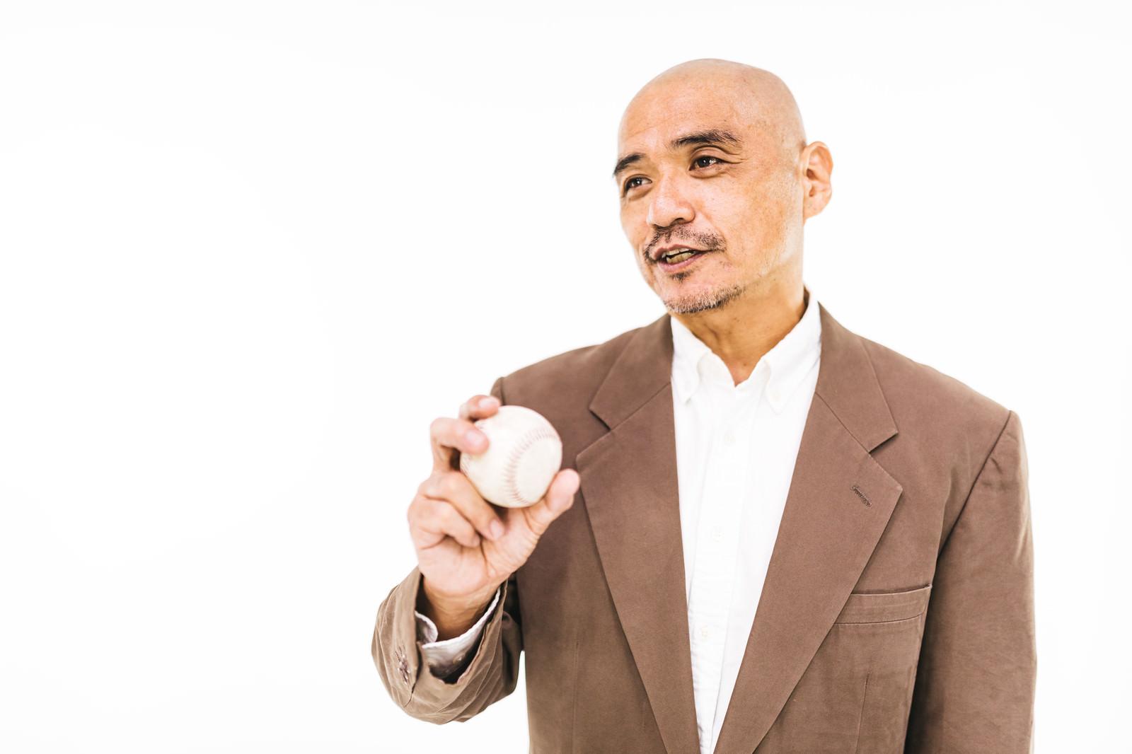 「硬球を持ってコメントする野球解説者」の写真[モデル:よたか]