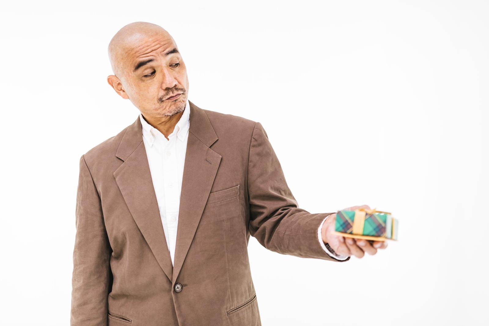 「恥ずかしげにプレゼントを渡すミドル」の写真[モデル:よたか]
