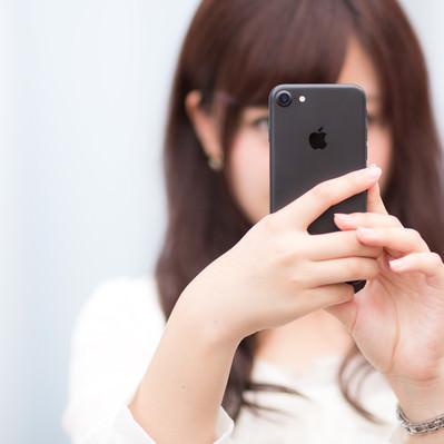 「マットブラックカラーのスマートフォンを操作する女性」の写真素材