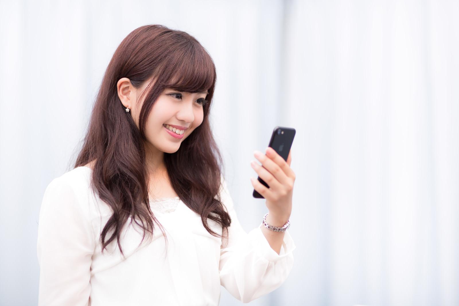 「新しいスマートフォンの高色域ディスプレイにご満悦のキラキラ女性」の写真[モデル:河村友歌]