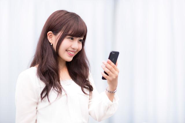 新しいスマートフォンの高色域ディスプレイにご満悦のキラキラ女性の写真