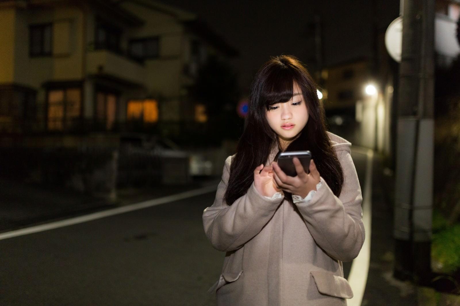 「深夜に歩きスマホをする女の子」の写真[モデル:河村友歌]