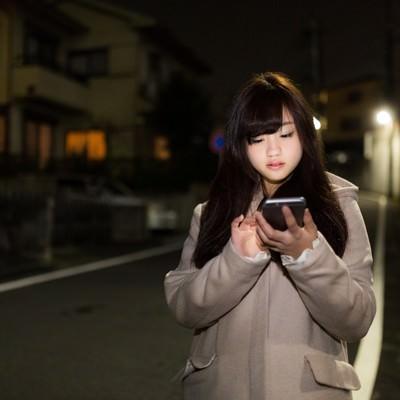 「深夜に歩きスマホをする女の子」の写真素材