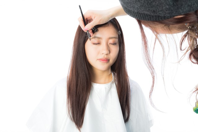 アイメイクを引く美容師の写真