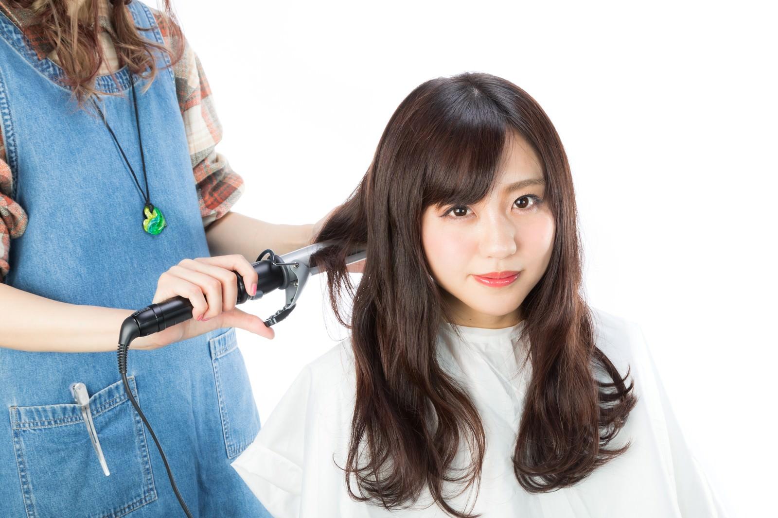 「後ろ髪を巻く美容師」の写真[モデル:河村友歌]