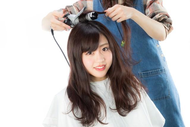 サロンモデルの髪の根元を巻く美容師の写真