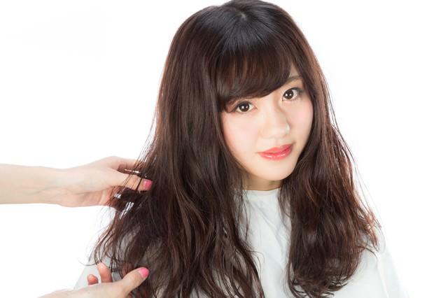 巻いた髪に整髪剤をつけるの写真