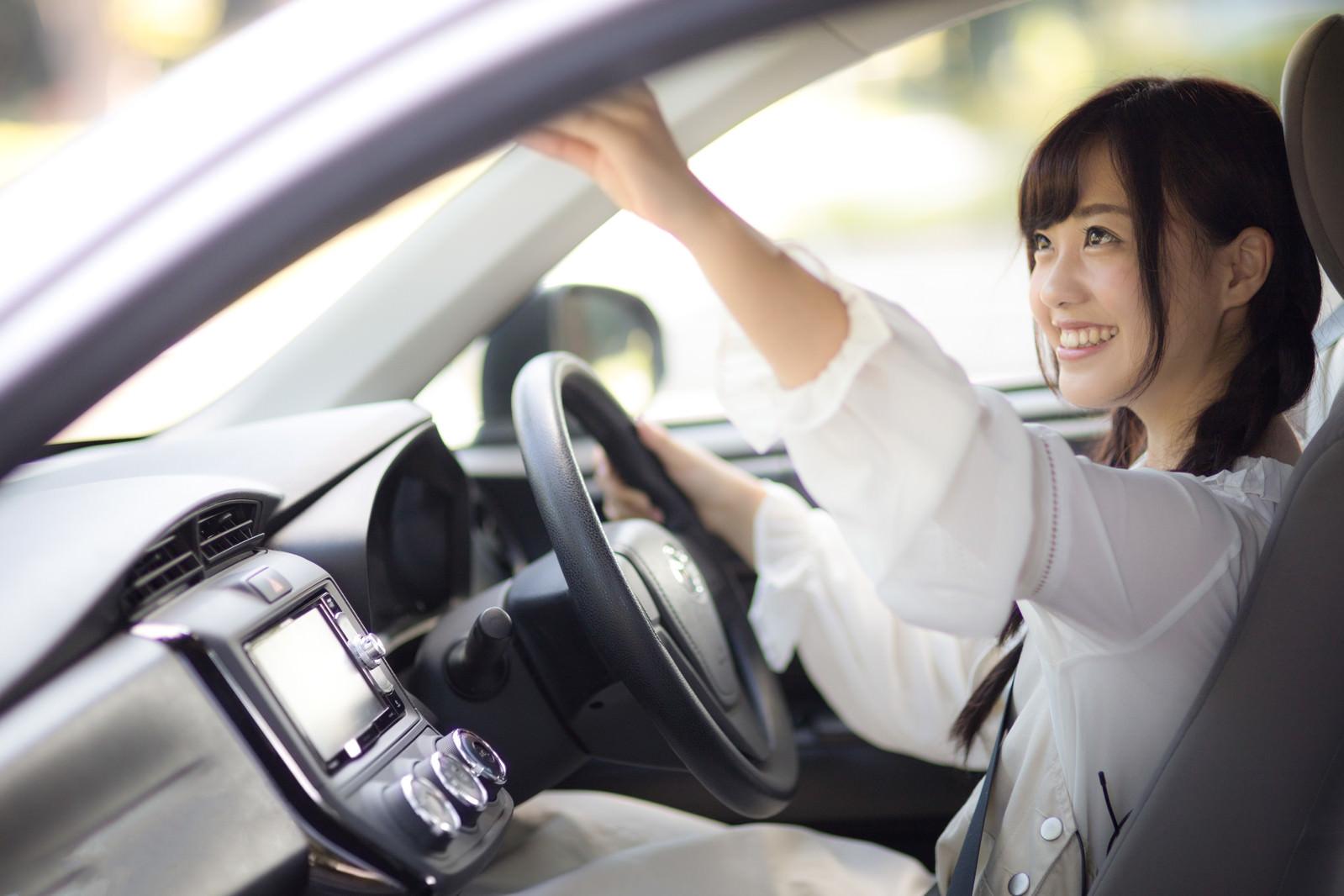 「車内のバックミラーを調整する女子車内のバックミラーを調整する女子」[モデル:河村友歌]のフリー写真素材を拡大