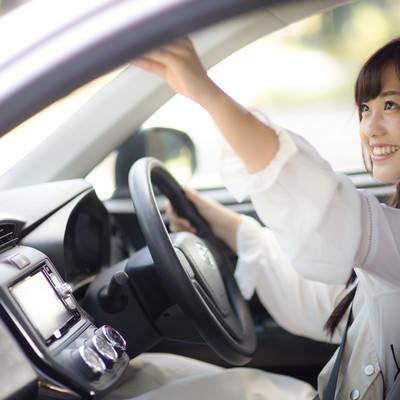 「車内のバックミラーを調整する女子」の写真素材