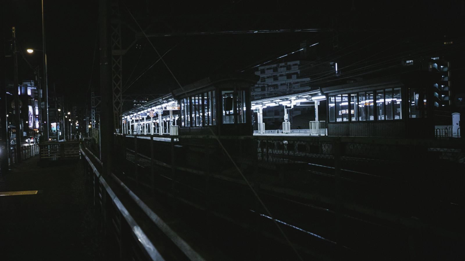 「照明が灯る無人の駅ホーム」の写真