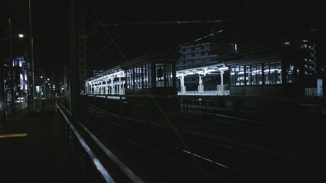 照明が灯る無人の駅ホームの写真