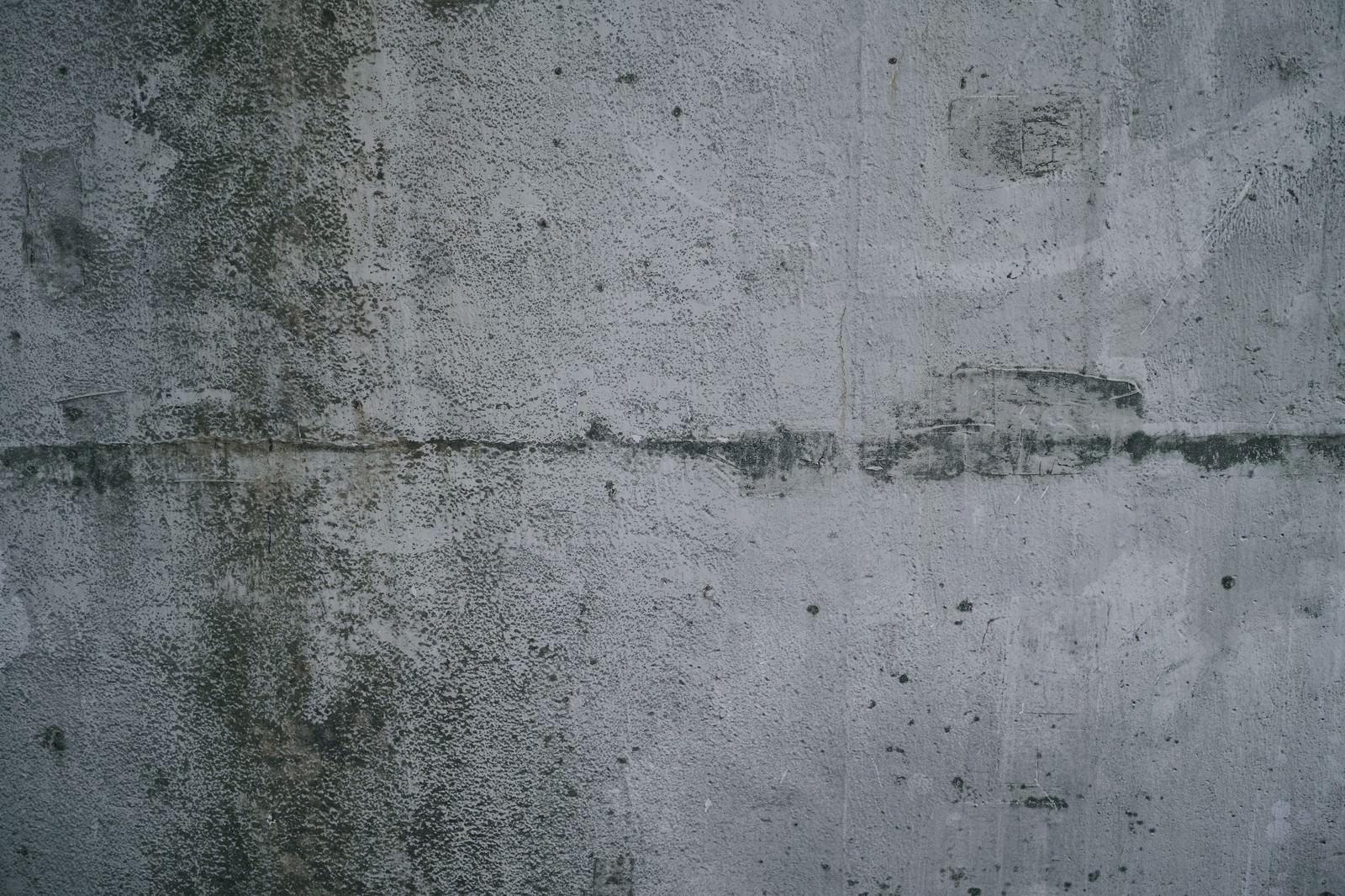「汚れに薄っすらと落書き跡が浮いたコンクリート壁(テクスチャ)」の写真