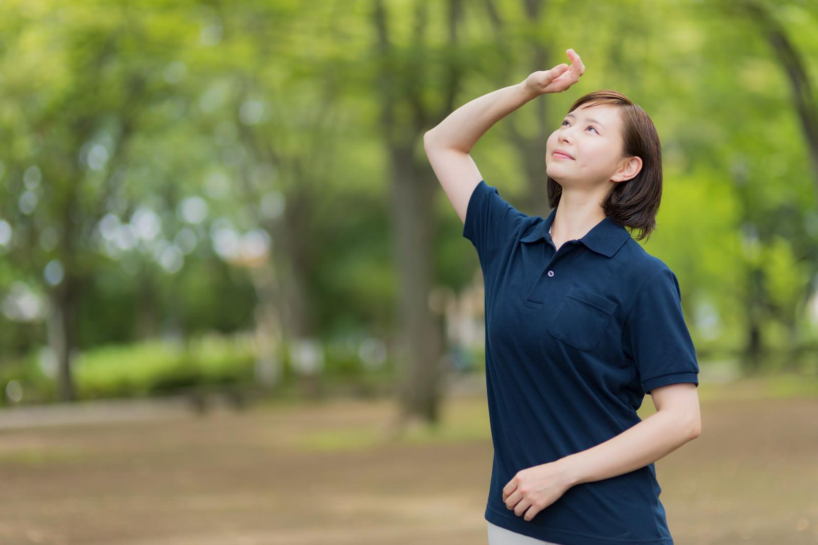 「森林の公園で木漏れ日を見上げる介護士さん」の写真[モデル:yumiko]