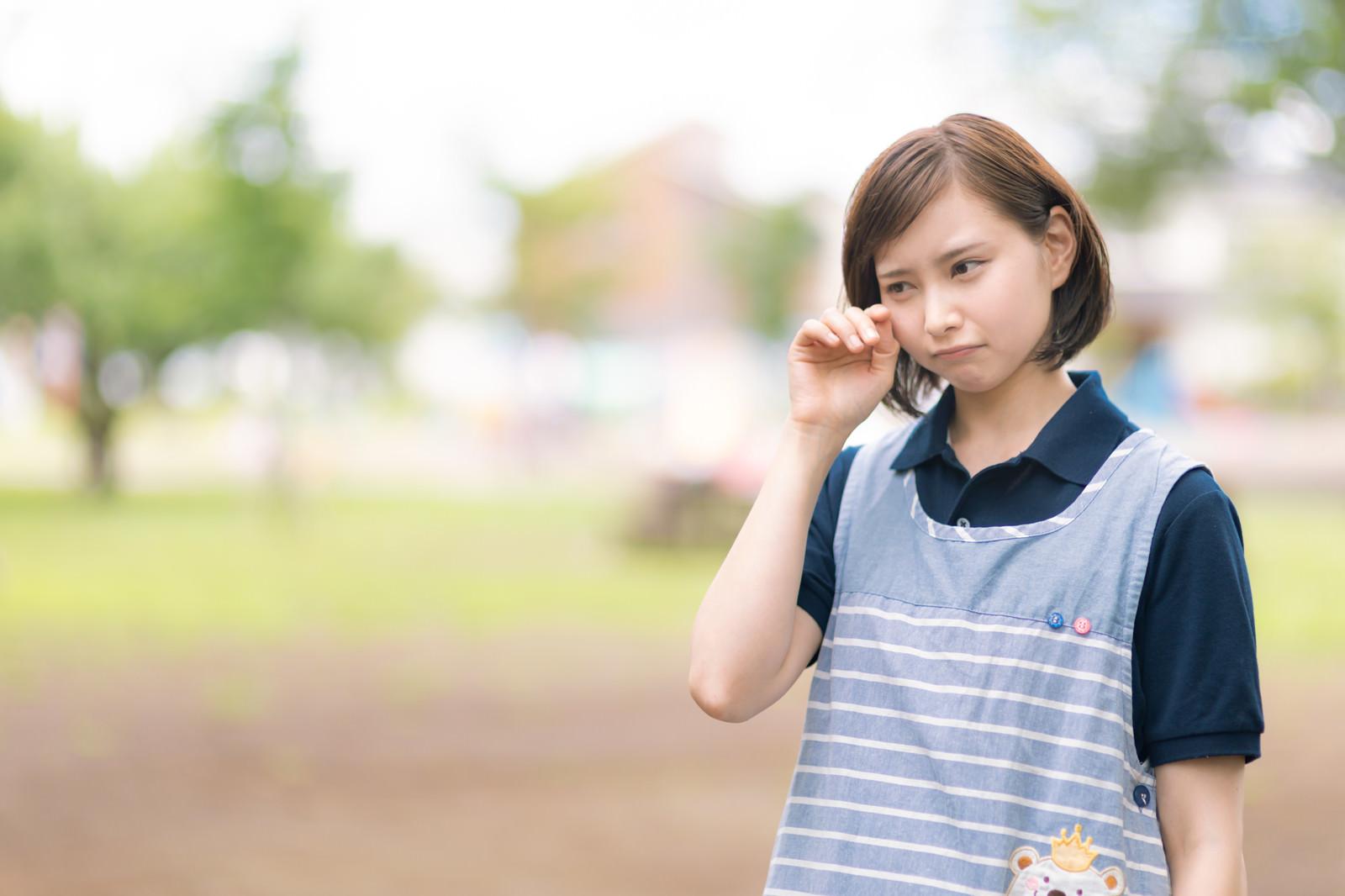 「つらくて涙を流す介護士」の写真[モデル:yumiko]
