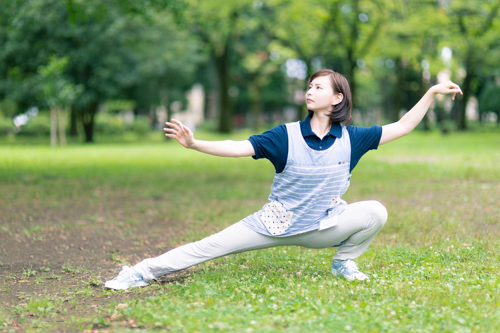 「早朝の公園でポーズを取る介護士さん」の写真[モデル:yumiko]