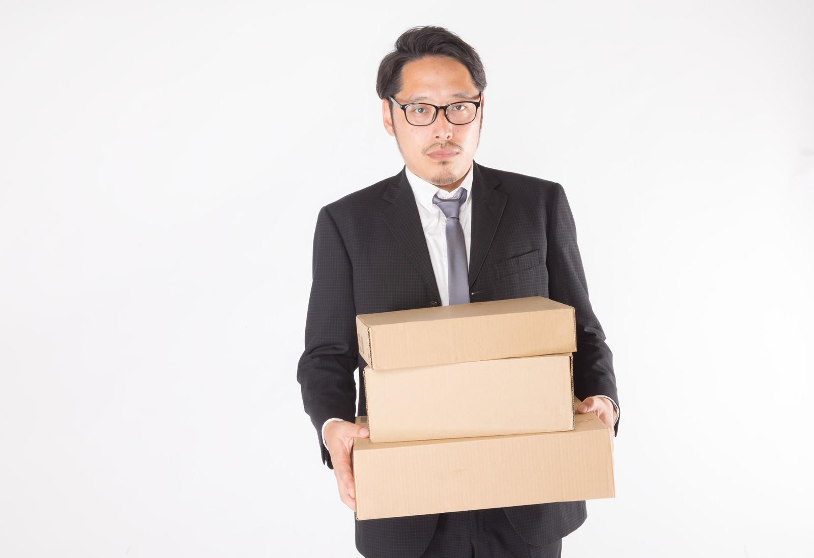「届いたダンボールを運ぶ総務部長」の写真[モデル:ゆうせい]