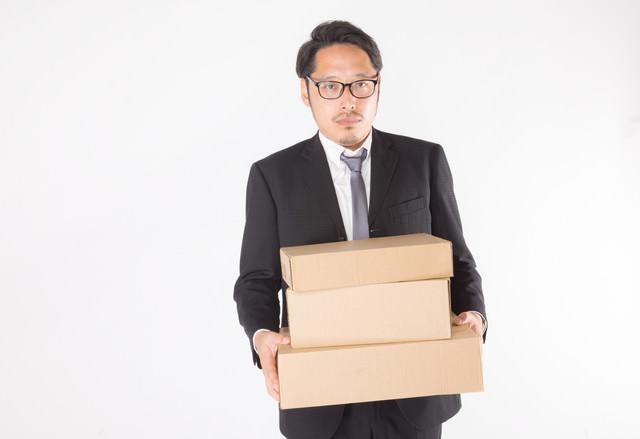 届いたダンボールを運ぶ総務部長の写真