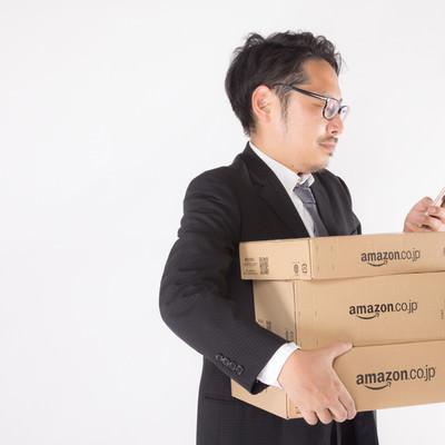 「届いた商品と発注した内容を確認する会社員」の写真素材