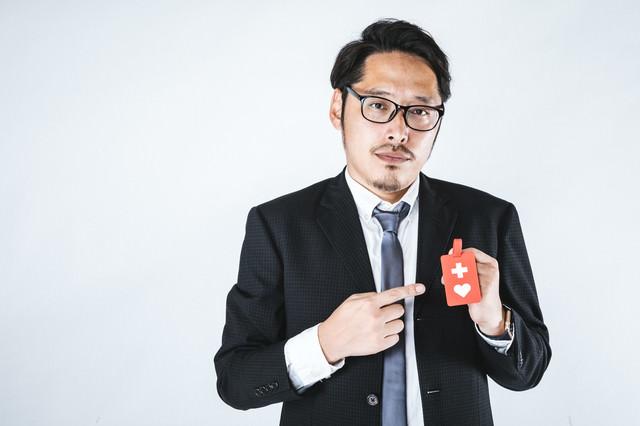 ヘルプマークを持った会社員の男性の写真