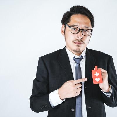 「ヘルプマークを持った会社員の男性」の写真素材