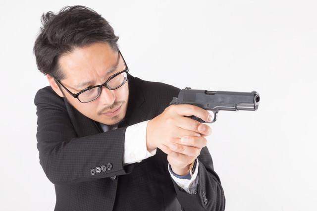 拳銃を向けるスーツ姿の会社員の写真