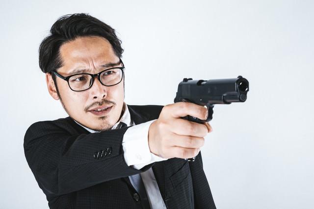 ガン・フーアクション風に拳銃を構えるスーツ姿の男性の写真