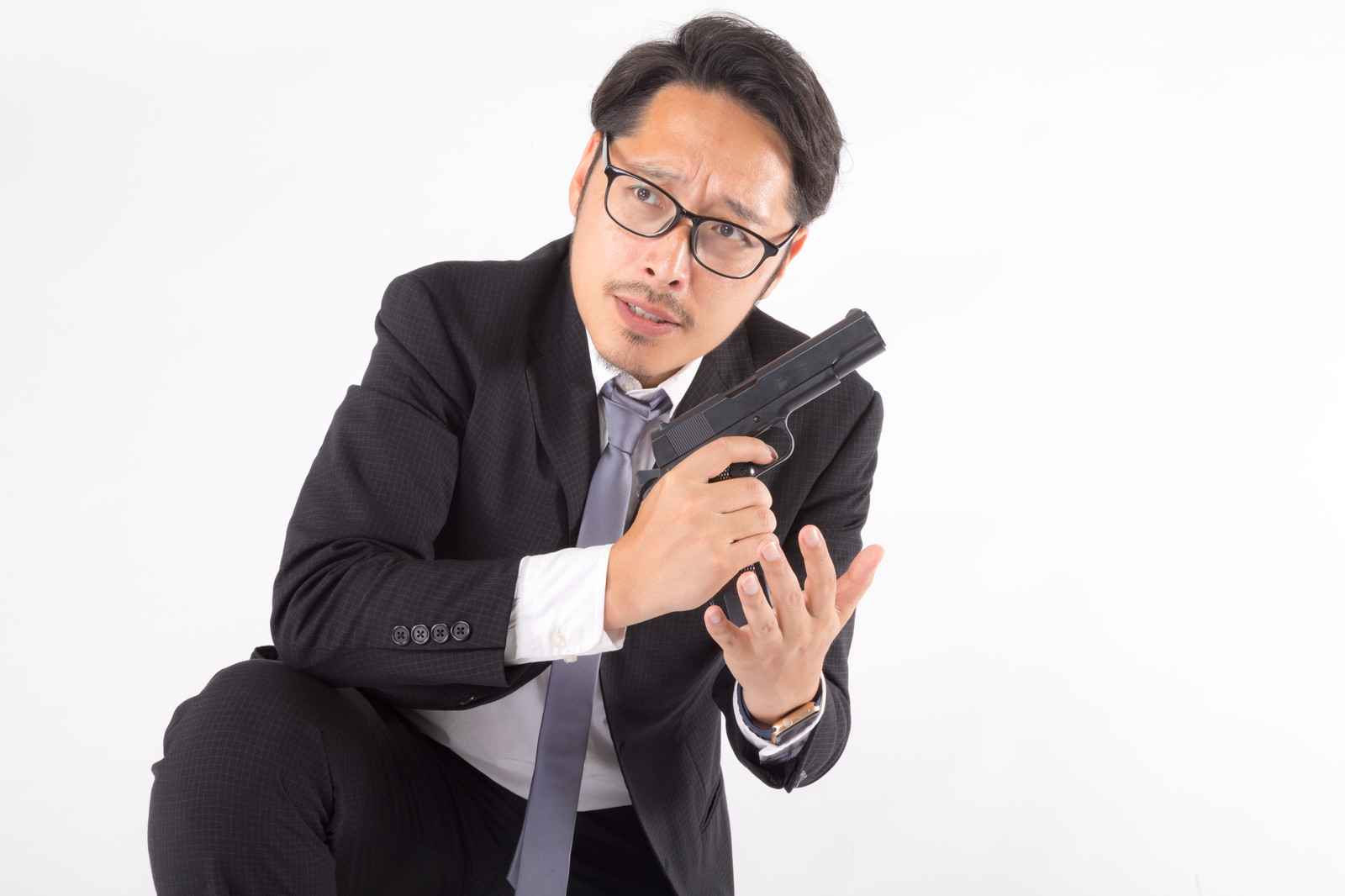 「辺りの様子をうかがいながら弾倉を装填する会社員」の写真[モデル:ゆうせい]