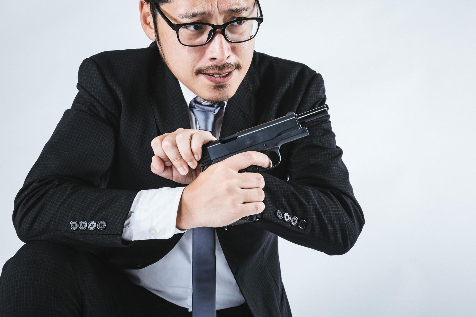 「拳銃をリロードするスーツ姿の男性」の写真[モデル:ゆうせい]
