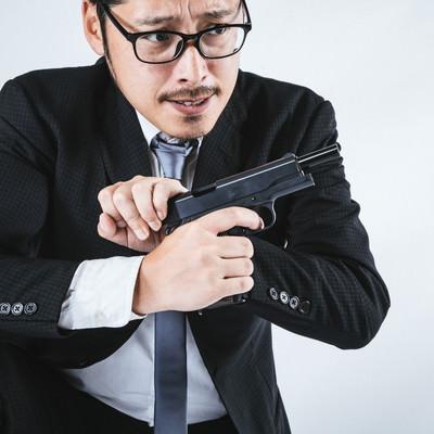 「拳銃をリロードするスーツ姿の男性」の写真素材