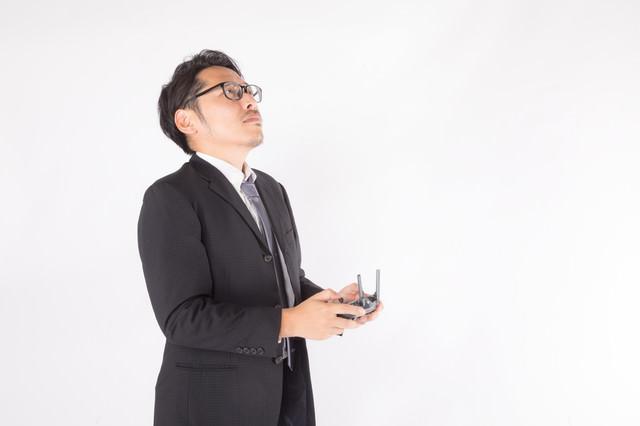 ドローンを操縦する会社役員の写真