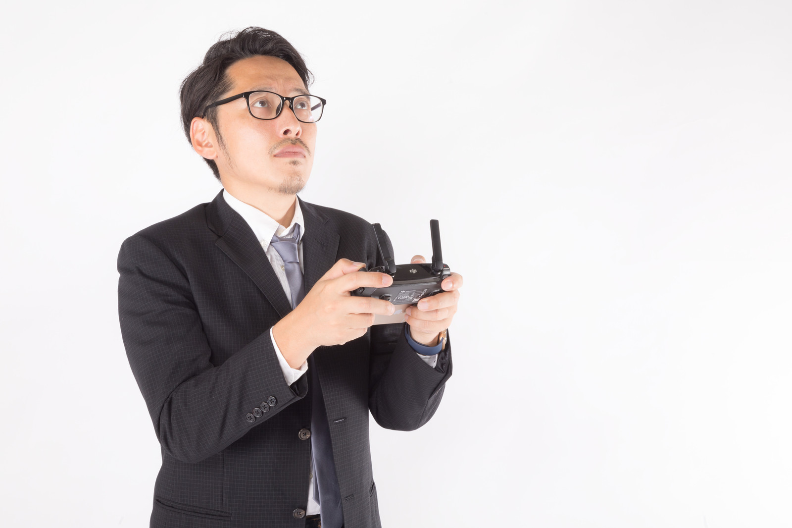 「スーツ姿のドローン操縦士」の写真[モデル:ゆうせい]