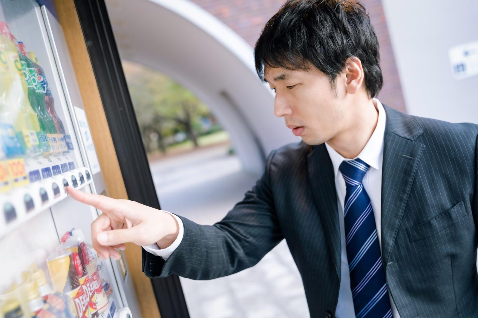 「自動販売機で飲み物を買う男性」の写真[モデル:大川竜弥]