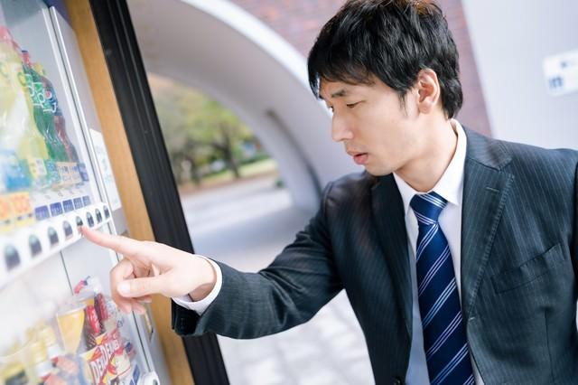 自動販売機で飲み物を買う男性の写真