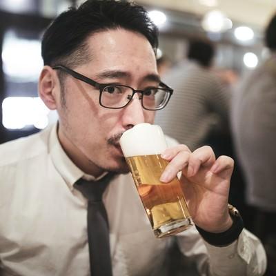 乾杯前にこっそり飲む男性の写真