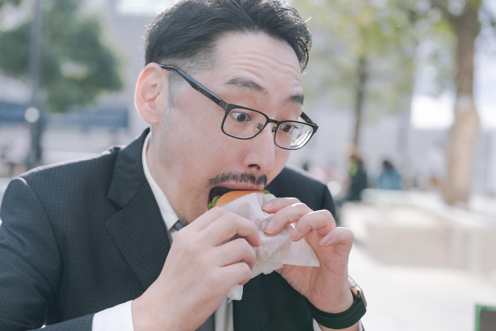 「ハンバーガーにかぶりつく男性社員」の写真[モデル:ゆうせい]