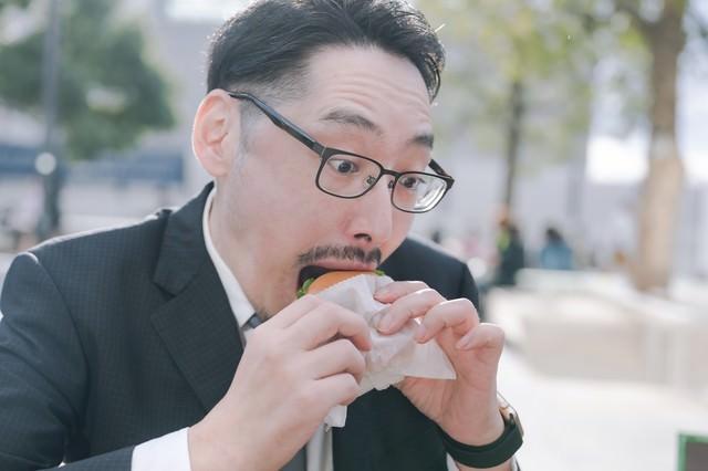 ハンバーガーにかぶりつく男性社員の写真