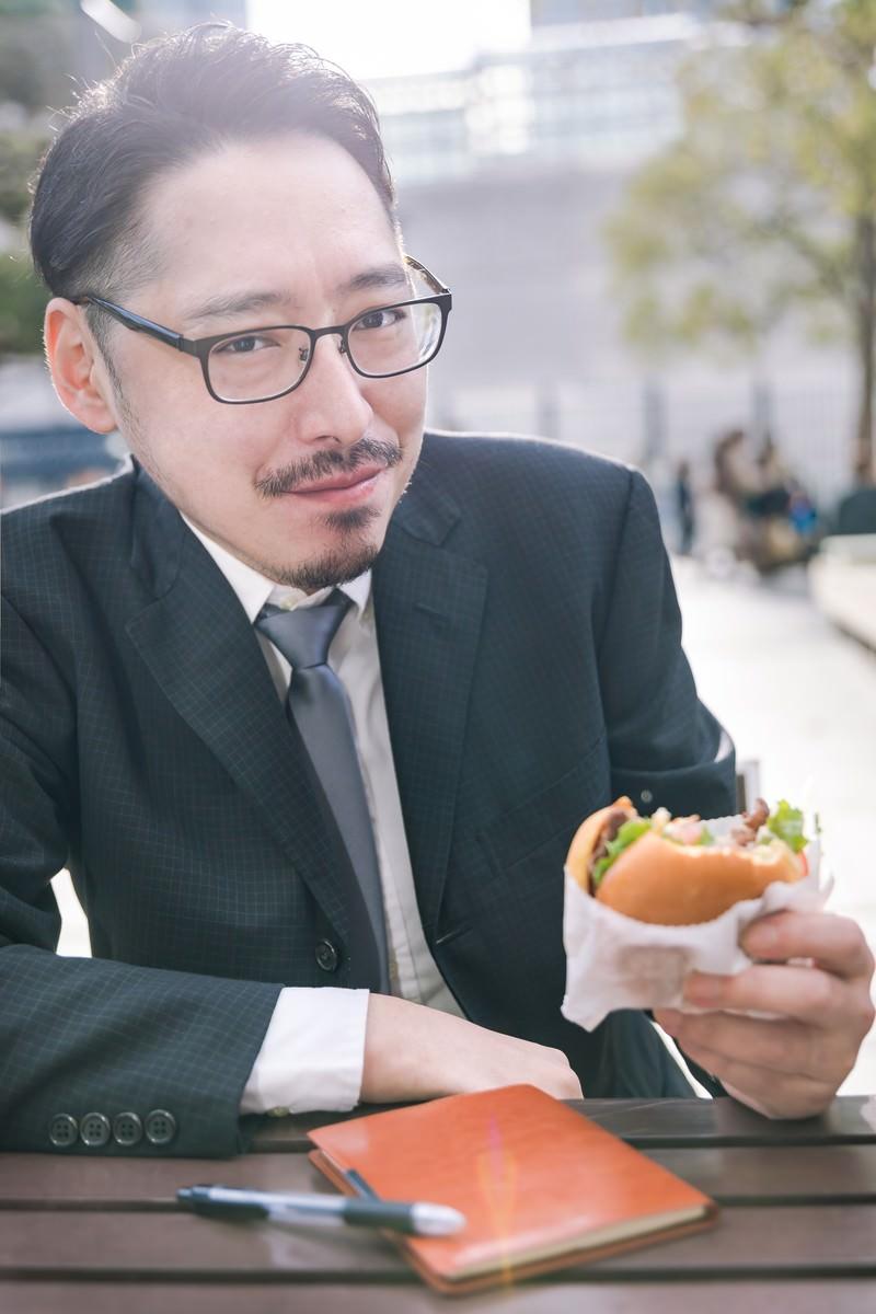 「ハンバーガーを食すグルメライター」の写真[モデル:ゆうせい]