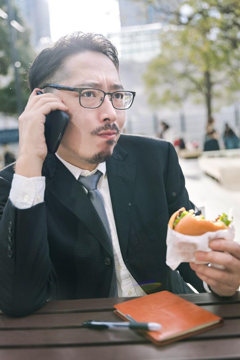 「食事中もスマートフォンが手放せないビジネスマン」の写真[モデル:ゆうせい]