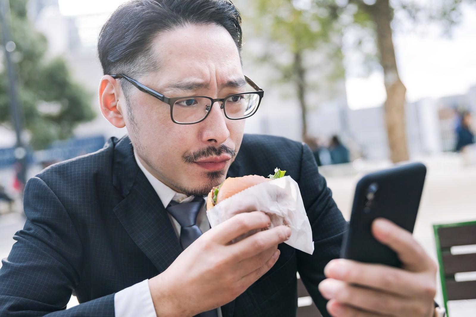 「グルメアプリにレビューを投稿する男性」の写真[モデル:ゆうせい]